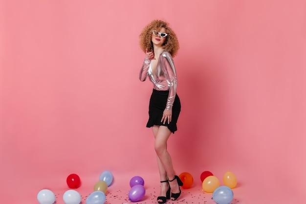 Stijlvolle diva in glanzende top en zwarte rok blaast kus. meisje in zonnebril koket poseren onder ballonnen op roze ruimte.