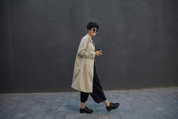 Stijlvolle donkerharige hipster vrouw met kort krullend haar wandelen in de stad tegen zwarte stadsmuur, gekleed in zwarte culottes en beige trenchcoat, papieren beker met afhaalkoffie vasthouden