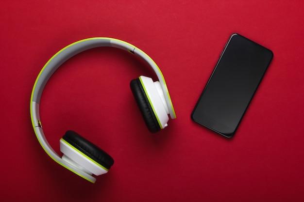 Stijlvolle draadloze stereohoofdtelefoon met smartphone op rood oppervlak