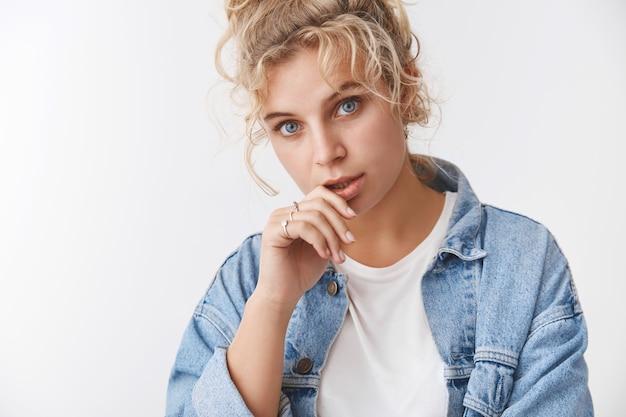 Stijlvolle duizendjarige aantrekkelijk brutaal blond meisje met krullen blauwe ogen kantelen hoofd blik gefocust zelfverzekerd ontroerend lip staren flirterig brutaal camera uitdrukken zelfverzekerd vastberaden assertieve houding