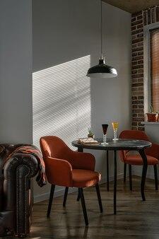 Stijlvolle eetkamer in loftstijl met zwarte houten tafel en rode fauteuils