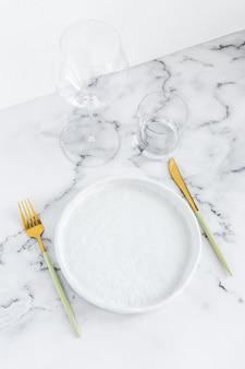Stijlvolle elegante tabel instelling met keramische plaat op witte marmeren achtergrond
