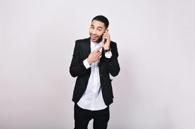 Stijlvolle elegante vrolijke man in wit overhemd en zwarte jas praten over de telefoon, glimlachend. zaken, succesvolle zakenman, opgewekte stemming, werk, vergadering.