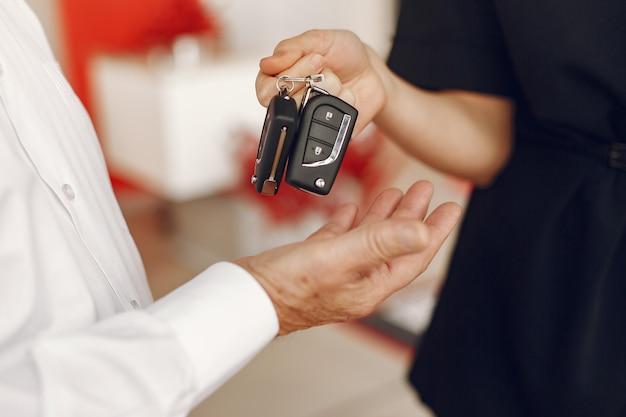Stijlvolle en elegante oude man in een auto salon