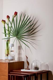Stijlvolle en florale compositie van prachtige bloemen in moderne vazen op de retro houten commode met elegante accessoires. bloesemconcept met schaduwen op de beige muur. interieur ontwerp. sjabloon.