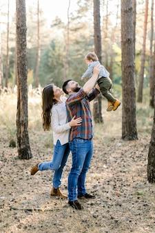 Stijlvolle en gelukkige familie in vrijetijdskleding, vader, moeder en zoontje wandelen in het herfstbos, hebben plezier en spelen met de baby