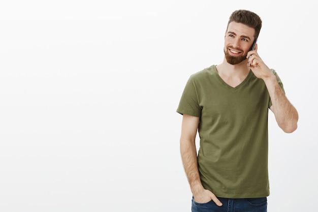 Stijlvolle en zelfverzekerde knappe bebaarde mannelijke ondernemer die op smartphone lacht en lacht genietend van gesprek kijkend naar linkerbovenhoek over witte muur