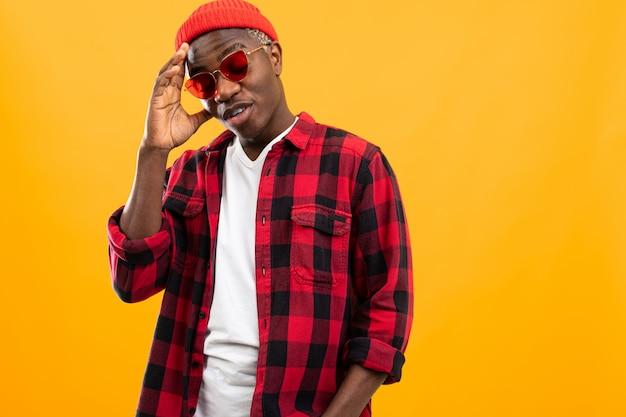 Stijlvolle ernstige zwarte afrikaanse man in rode retro bril en een geruite overhemd n oranje met kopie ruimte voor reclame
