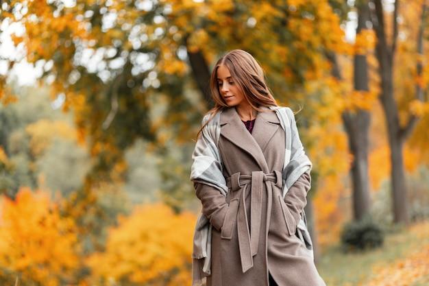 Stijlvolle europese jonge vrouw in een modieuze jas in een trendy geruite gebreide sjaal wandelingen in het park met oranje gebladerte. aantrekkelijk meisje ontspant buiten op een warme dag in oktober. herfst kleding.