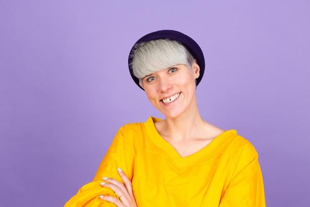 Stijlvolle europese vrouw op paarse muur. blij gezicht lachend met gekruiste armen kijken naar de camera