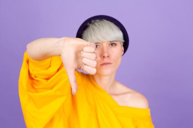Stijlvolle europese vrouw op paarse muur. ziet er ongelukkig en boos uit en toont afwijzing en negatief met duim omlaag gebaar. slechte uitdrukking