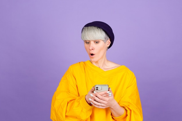 Stijlvolle europese vrouw op paarse muur