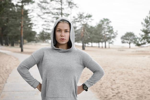 Stijlvolle europese vrouwelijke atleet die voor marathon voorbereidingen treft, cardio-activiteit ochtendroutine in bos doet. zelfverzekerde, zelfbepaalde jonge sportvrouw die buitenshuis traint, hand in hand op haar middel