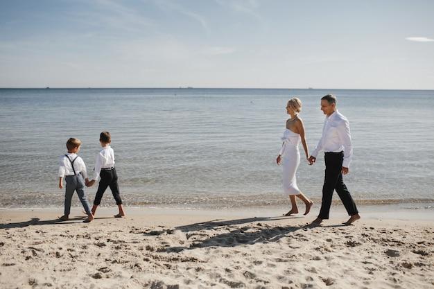 Stijlvolle familie loopt op het strand bij de kalme zee, ouders en kinderen houden elkaars hand vast