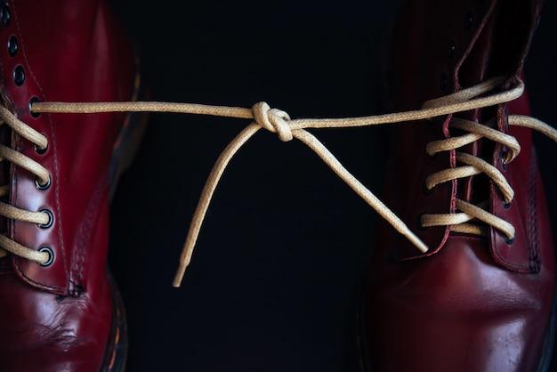 Stijlvolle felrode schoenen met dikke witte veters aan elkaar gebonden, close-up