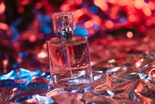 Stijlvolle fles damesparfum in neonlichten op de folie met glanzend verfrommeld oppervlak