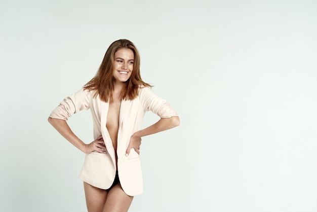 Stijlvolle foto van een model in een witte studio. jonge vrouw in ondergoed en een jasje op een naakt lichaam. mode.