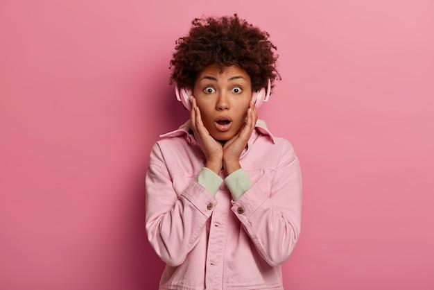 Stijlvolle gekrulde haren jonge vrouw houdt handen op de wangen, draagt een roze jasje, luistert naar radio online, maakt gebruik van draadloze koptelefoons, heeft geschokt gezichtsuitdrukking