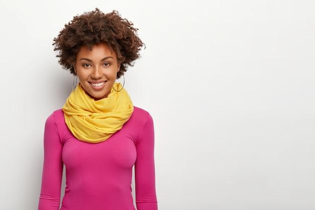Stijlvolle, gekrulde vrouw met knapperig kapsel, draagt gele sjaal en roze poloneck, glimlacht positief