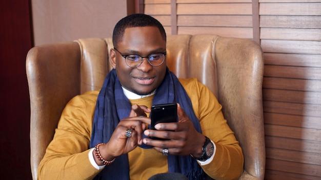 Stijlvolle gelukkig afro-amerikaanse man zit in een stoel met een sigaar