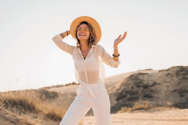 Stijlvolle gelukkig mooie lachende vrouw poseren in woestijnzand in witte outfit stro hoed en zonnebril dragen op zonsondergang