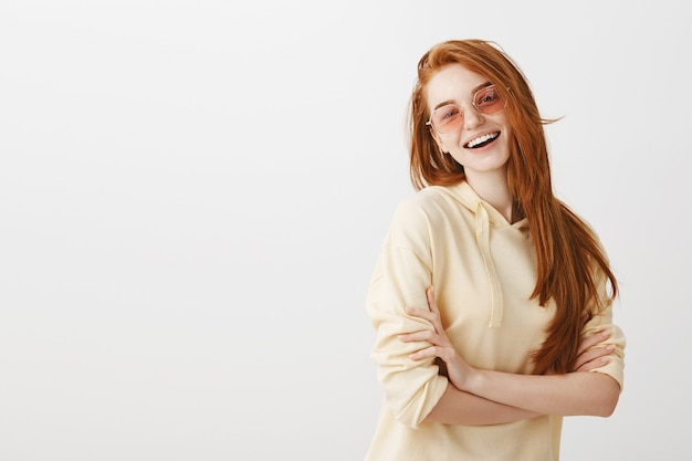 Stijlvolle gelukkig prachtige roodharige meisje kruis armen borst en glimlachen