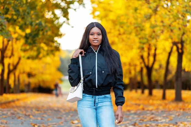 Stijlvolle, gelukkige afro-amerikaanse vrouw in een zwart jasje en een spijkerbroek met witte tas loopt in het park met verbazingwekkende gouden herfstbladeren