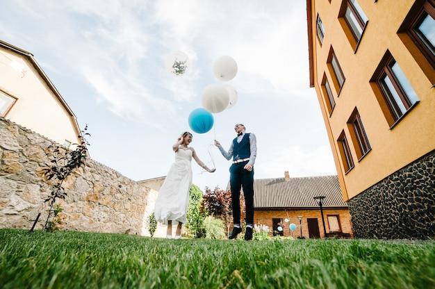 Stijlvolle gelukkige bruid en bruidegom houden ballonnen in handen en springen, poses