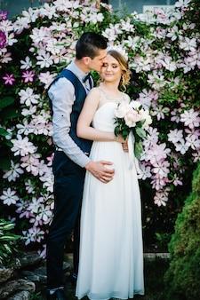 Stijlvolle gelukkige bruid met boeket van pioenrozen met een kroon en bruidegom.