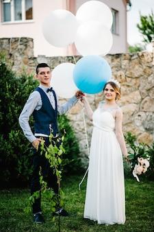 Stijlvolle gelukkige bruid met een boeket pioenrozen en bruidegom houden ballonnen in handen