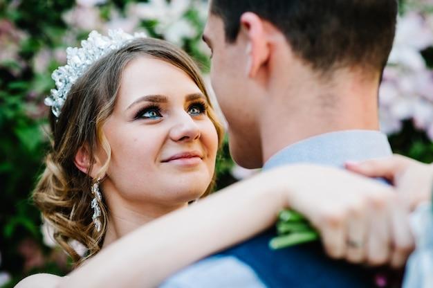 Stijlvolle gelukkige bruid met kroon en bruidegom. mooie vrolijke ogen, mooie make-up.