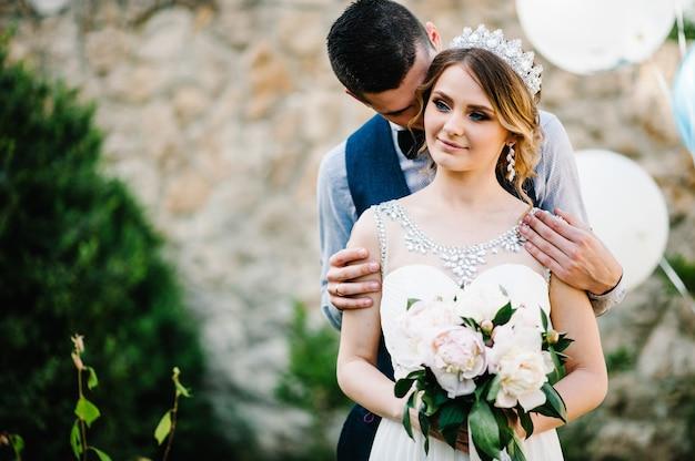 Stijlvolle gelukkige bruid, vrouw met kroon en bruidegom, man