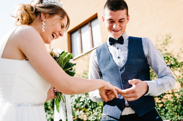 Stijlvolle gelukkige bruidegom dragen gouden ring aan de vinger van de bruid. huwelijksceremonie.