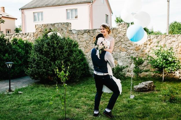 Stijlvolle gelukkige bruidegom houdt op handen bruid en knuffel. dans en draai.