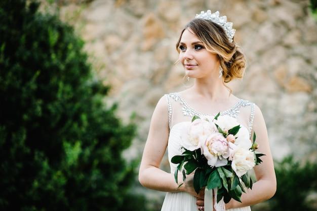 Stijlvolle gelukkige glimlach bruid met boeket van pioenrozen met kroon vormt op het oppervlak op de binnenplaats van huis
