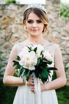 Stijlvolle gelukkige glimlach bruid met boeket van pioenrozen. natuur.