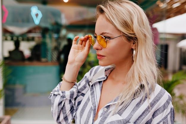 Stijlvolle gelukkige jonge vrouw ronde bril en gestripte shirt