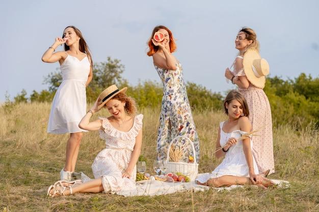 Stijlvolle gelukkige vriendinnen plezier op outdoor retro-stijl picknick partij