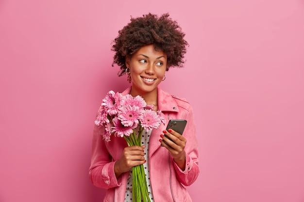 Stijlvolle gelukkige vrouw bloemist vormt met gerbera boeket en smartphone