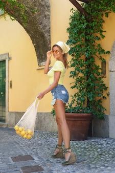 Stijlvolle gelukkige vrouw die door de straten van de kleine italiaanse stad loopt