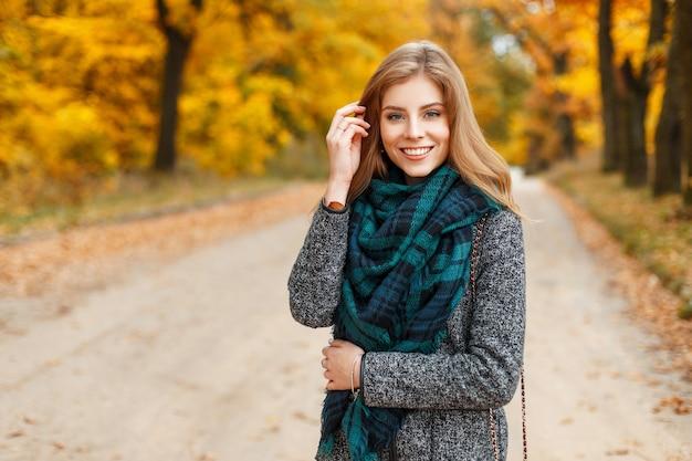 Stijlvolle gelukkige vrouw in trendy jas en sjaal wandelen in herfst park
