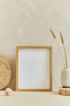 Stijlvolle, gezellige minimalistische interieurontwerpcompositie met mock-up posterframe, natuurlijke materialen als hout en marmer, droge planten en persoonlijke accessoires. neutrale beige kleuren, sjabloon.