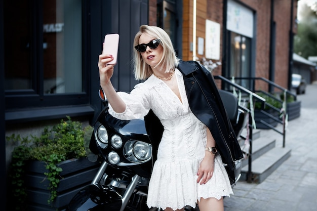 Stijlvolle girl biker in modieuze kleding (witte jurk, zwarte leren jassen, zonnebril)
