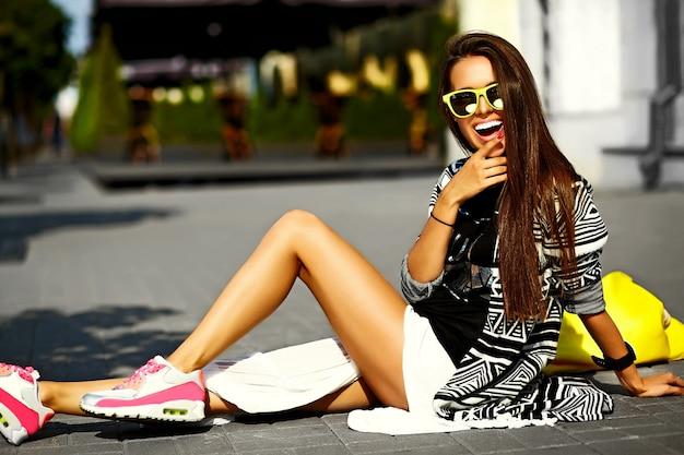 Stijlvolle glamour stijlvolle sexy lachende mooie jonge vrouw model in hipster zomer kleding zitten in de straat met winkelen fel gele tas