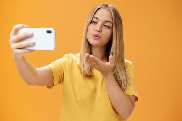 Stijlvolle glamoureuze vrouwelijke modeblogger die video-opname via smartphone beëindigt door luchtkus te verzenden, selfie te nemen met sensuele en zelfverzekerde blik op scherm poseren over oranje muur