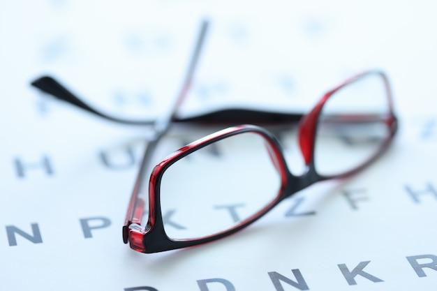Stijlvolle glazen in zwarte en rode monturen liggen op oogheelkundige tafelselectie van brilconcept
