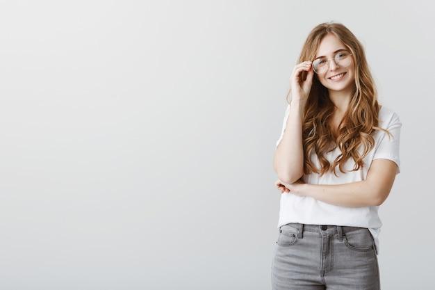 Stijlvolle glimlachende blonde vrouwelijke student die in glazen gelukkig kijkt