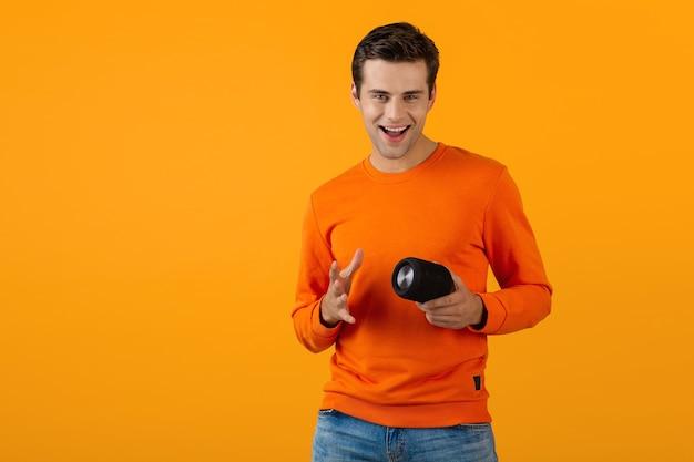 Stijlvolle glimlachende jongeman in oranje trui met draadloze luidspreker die graag naar muziek luistert met plezier