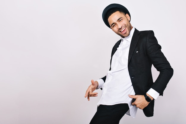 Stijlvolle glimlachende man in pak, hoed met plezier. vrije tijd, vrolijke stemming, vreugde, geluk, danseres, moderne geïsoleerde zakenman.