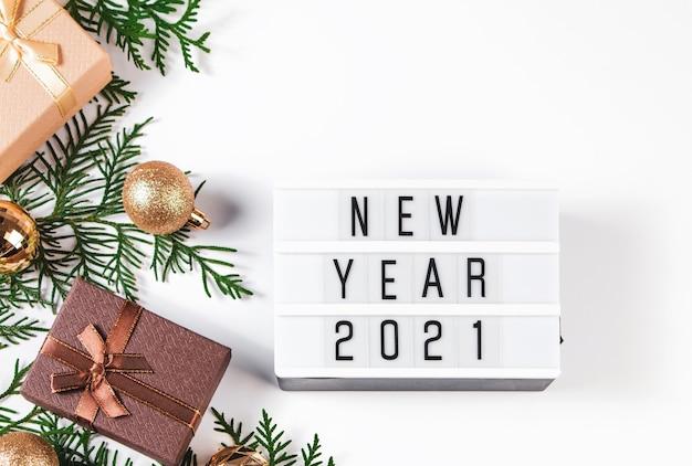 Stijlvolle gouden kerstballen en geschenken op witte achtergrond. new year's samenstelling, plaats voor tekst.